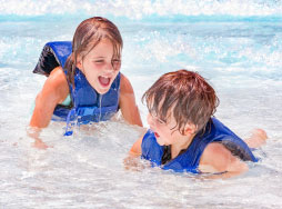 boy and girl wearing life jackets while playing in pool